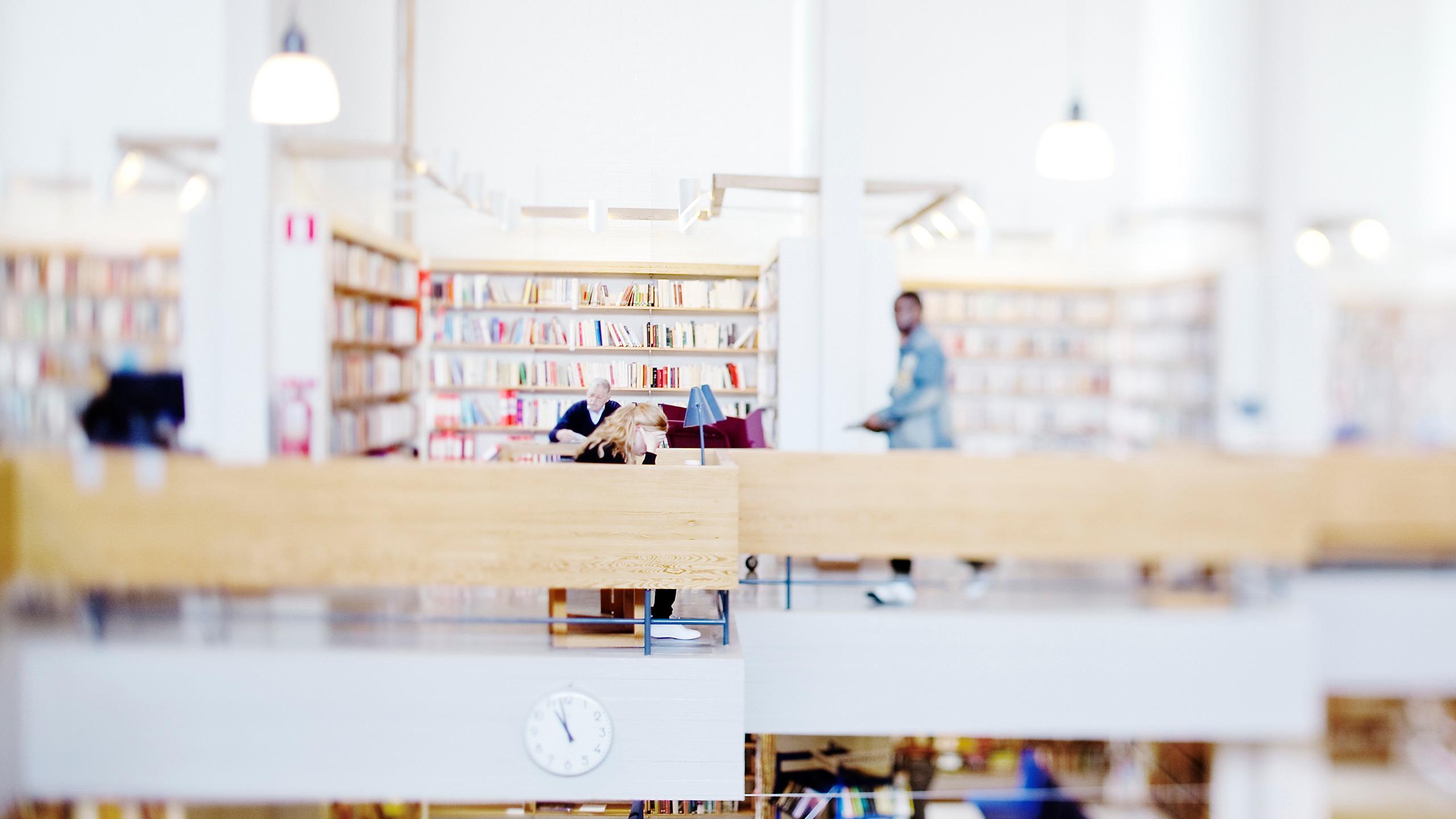 Personer läser böcker på stadsbibliotekets övre plan