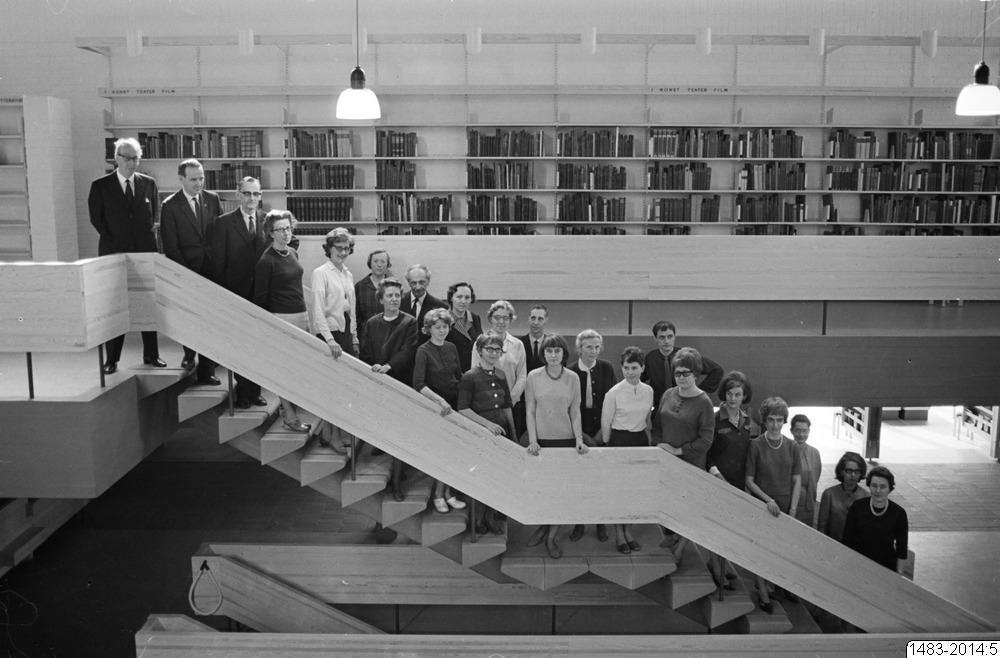 Svartvit bild med personer som står uppradade i trappan på stadsbiblioteket