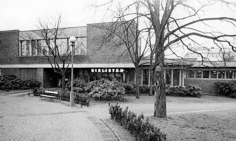 Svartvit bild som visar bibliotekets entré och delar av utemiljön framför