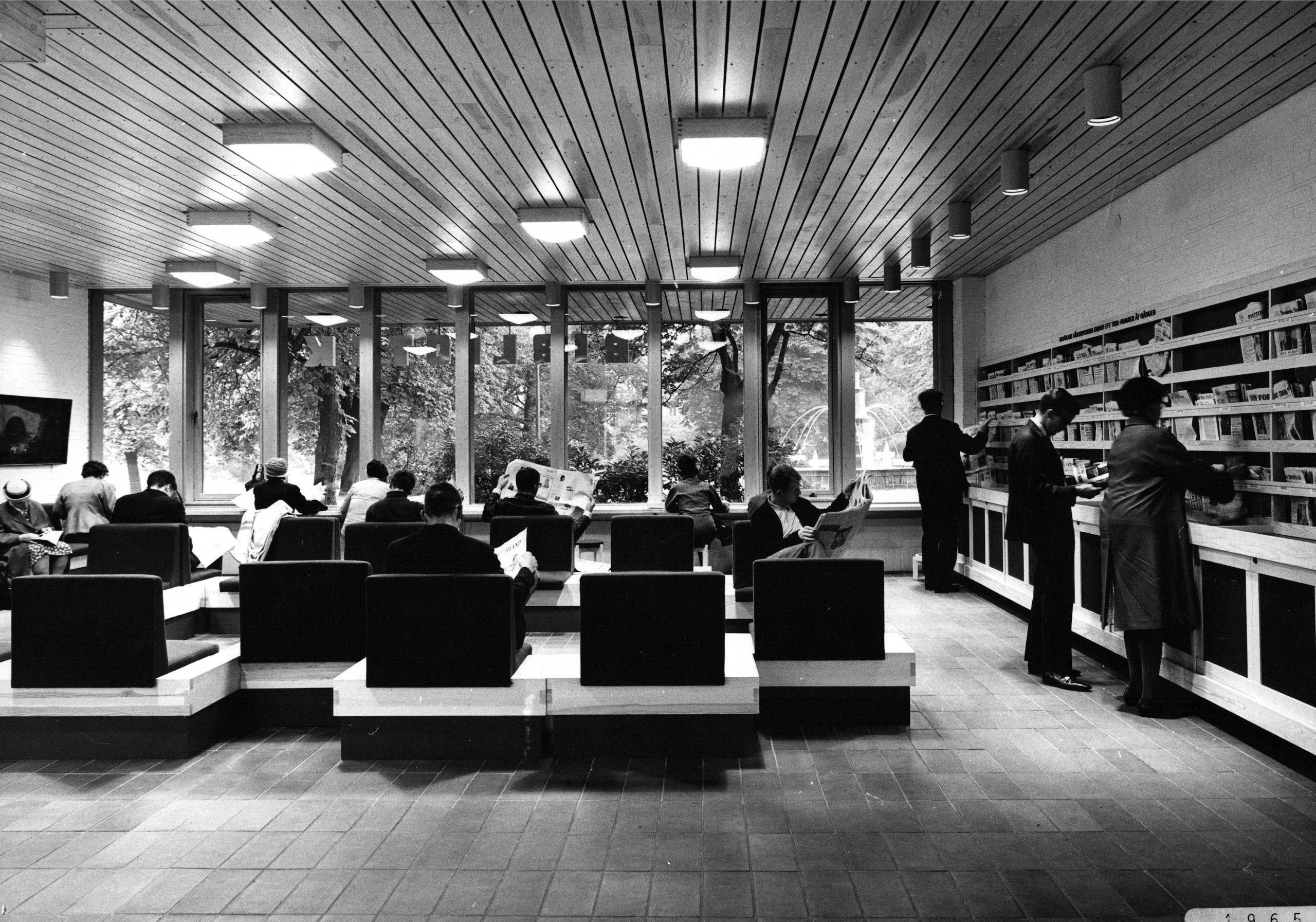Svartvit bild med personer som sitter ner och läser tidningar